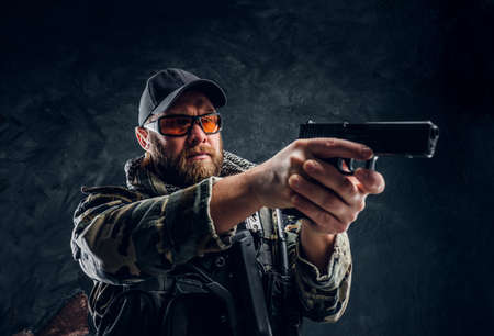 Special forces soldier holding a gun and aiming at the enemy. Studio photo against a dark textured wall