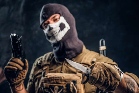 A terrorist in a military uniform and a skull balaclava holding a pistol and a knife and looks at the camera with a menacing look. Focusing the camera on the knife