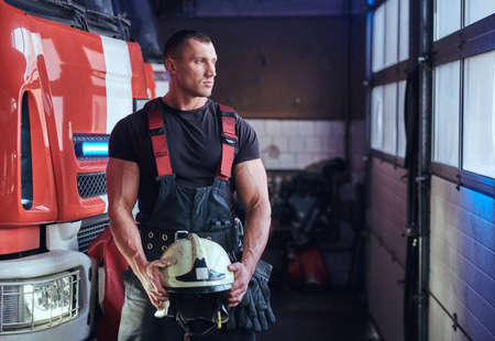 Muscular fireman holding a protective helmet in a garage of a fire department, standing next to a fire engine and looking outside