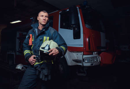 Portrait of a brave young fireman wearing protective uniform standing next to a fire engine in a garage of a fire department Imagens