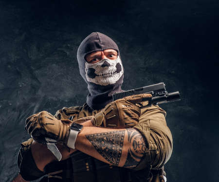 A terrorist in a military uniform and a skull balaclava holding a pistol and a knife and looks at the camera with a menacing look. Studio photo against a dark textured wall