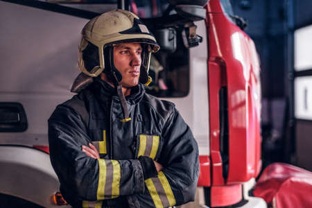 A brave fireman wearing protective uniform standing next to a fire engine in a garage of a fire department, crossed arms and looking sideways