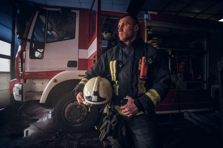 Handsome fireman wearing uniform holding a helmet and looking sideways while standing near a fire truck in a garage of a fire department