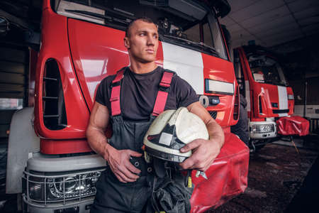 Muscular fireman holding a protective helmet in a garage of a fire department, leaning on a fire engine and looking outside Stock Photo
