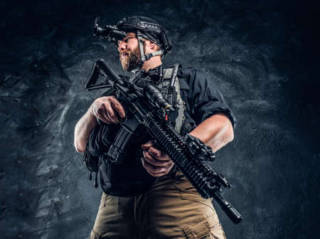 Bearded special forces soldier or private military contractor holding an assault rifle and observes the surroundings in night vision goggles. Studio photo against a dark textured wall