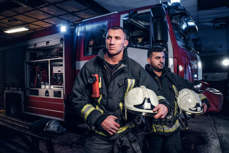 Two firemen wearing protective uniform standing next to a fire truck. Arrival on call at night time Imagens