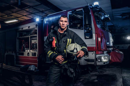 Handsome fireman wearing uniform holding a helmet and looking at a camera while standing near a fire truck in a garage of a fire department