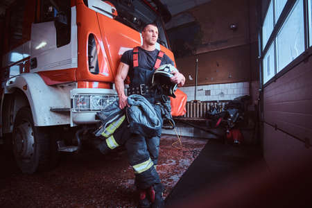 Fireman holding a jacket and protective helmet in a garage of a fire department, leaning on a fire engine and looking outside Stockfoto