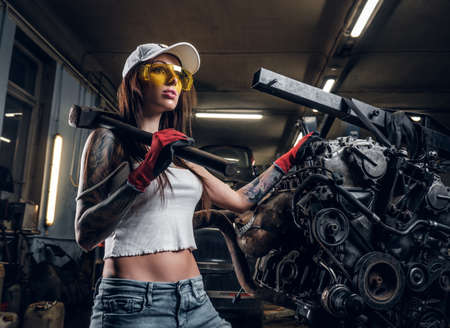 Stylish girl wearing cap and goggles posing with a steel hammer next to a car engine suspended on a hydraulic hoist in the workshop