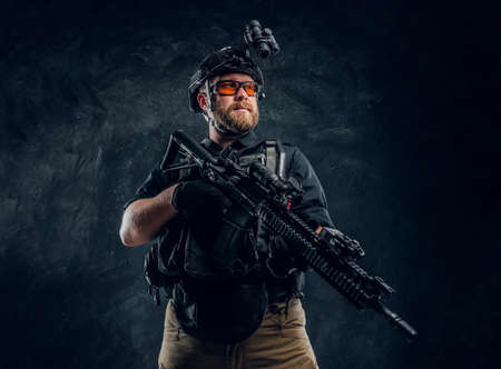 Bearded special forces soldier wearing body armor and helmet with night vision holding an assault rifle. Studio photo against a dark textured wall Stock Photo