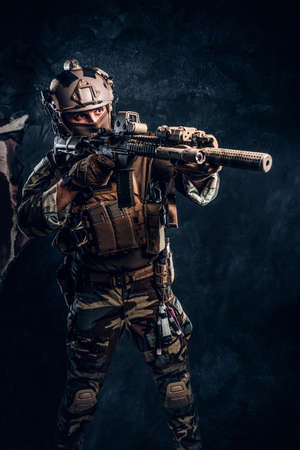 Elite unit, special forces soldier in camouflage uniform holding an assault rifle with a laser sight and aims at the target. Studio photo against a dark textured wall