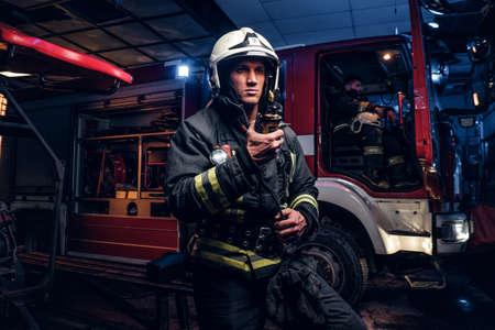 Nella notte sono arrivati i vigili del fuoco. Vigile del fuoco in uniforme protettiva in piedi accanto a un camion dei pompieri e parla alla radio