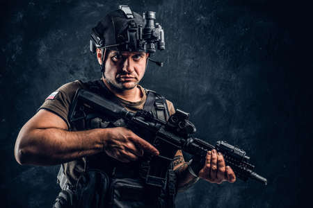 Brutal soldier of the Russian Federation wearing body armor and helmet with a night vision posing with an assault rifle. Studio photo against a dark textured wall