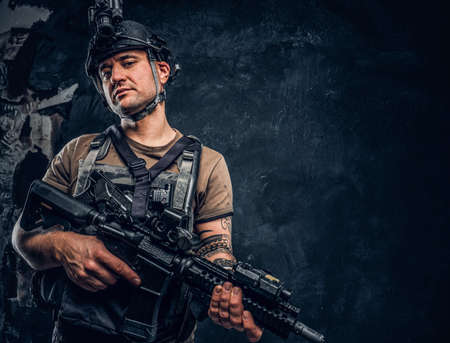 Brutal soldier in t-shirt with tattoo on his hand wearing body armor and helmet with a night vision posing with an assault rifle. Studio photo against a dark textured wall Imagens