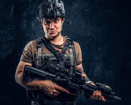 Man in t-shirt with tattoo on his hand wearing body armor and helmet with a night vision holding assault rifle and looking at a camera with a funny look. Studio photo against a dark textured wall Imagens