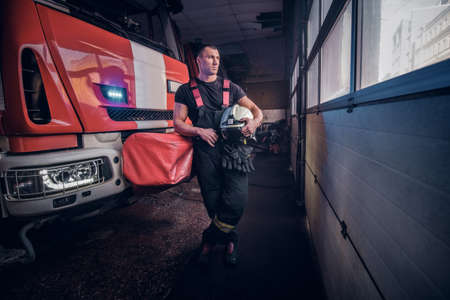 Fireman holding a jacket and protective helmet in a garage of a fire department, leaning on a fire engine and looking outside Stock Photo