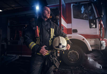 Handsome fireman wearing uniform looking outside while standing near a fire truck in a garage of a fire department