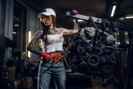 Female model with sexy tattooed body wearing a cap and protective goggles posing with a big wrench next to a car engine suspended on a hydraulic hoist in the workshop