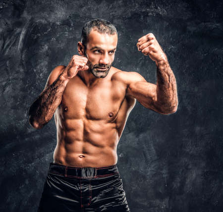 Professional fighter showing kick fighting technique. Studio photo against a dark textured wall