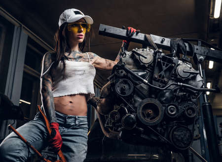 Sexual tattoed girl wearing cap and dirty clothes posing next to a car engine suspended on a hydraulic hoist in the workshop 免版税图像 - 118795223