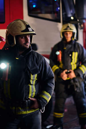 Two brave firemen wearing a protective uniform standing next to a fire truck. Arrival on call at night time