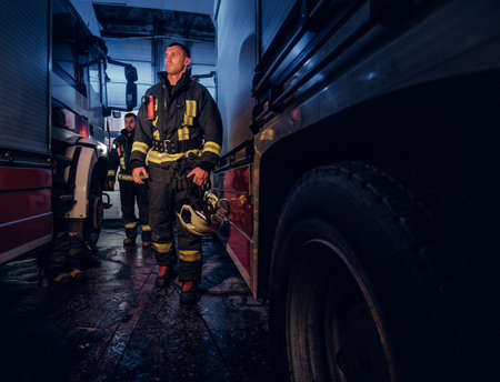 Full-length portrait of two brave firemen in protective uniform walking between two fire engines in the garage of the fire station Reklamní fotografie