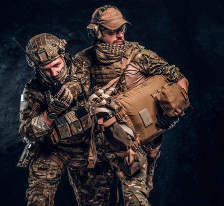 Combattre un conflit, une mission spéciale, une retraite. Un infirmier militaire sauve son coéquipier blessé en l'emportant hors du champ de bataille. Photo de studio contre un mur sombre Banque d'images
