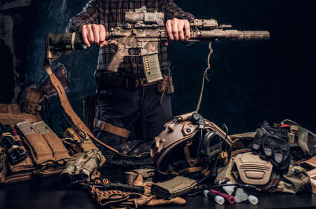 Man in a checkered shirt holding a assault rifle and showing his military uniform and equipment. Modern special forces equipment. Studio photo against a dark textured wall