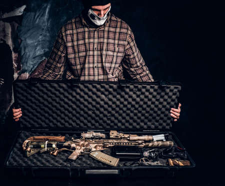 Illegal sale of weapons, black market, the criminal opens the case with an assault rifle and shows it to the buyer Stockfoto