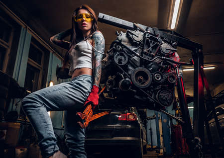 Stylish tattooed girl holding a big wrench and posing next to a car engine suspended on a hydraulic hoist in the workshop. Reklamní fotografie