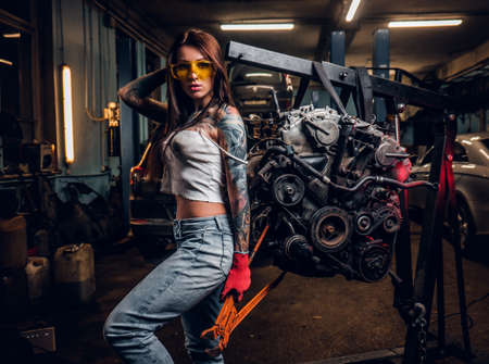 Stylish tattooed girl holding a big wrench and posing next to a car engine suspended on a hydraulic hoist in the workshop. Фото со стока
