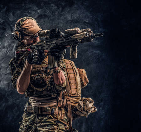The elite unit, special forces soldier in camouflage uniform holding an assault rifle with a laser sight and aims at the target. Studio photo against a dark textured wall