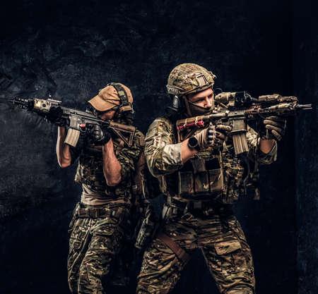 Contratistas de servicios de seguridad privados, la unidad especial de élite, soldados protectores completos que apuntan a los objetivos. Foto de estudio contra una pared oscura. Foto de archivo