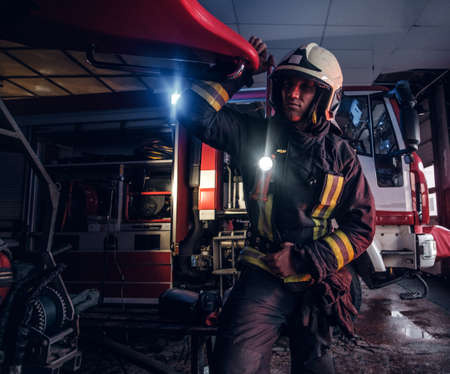 Fireman wearing a protective uniform with flashlight included working in a fire station garage Stockfoto