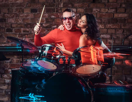 Beautiful girl hugs her idol who plays on a drum set in nightclub against a brick wall Imagens