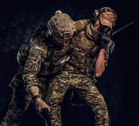 Combat conflict, special mission. The military soldier carrying teammate out of the battlefield. Studio photo against a dark textured wall