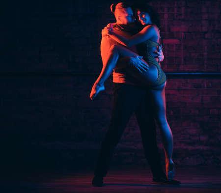 Bailarines profesionales realizan una danza incendiaria en una habitación oscura con iluminación. Foto de archivo