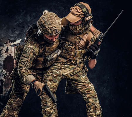 Combat conflict, special mission, retreat. The military soldier carrying teammate while he shoots back. Studio photo against a dark wall Banque d'images