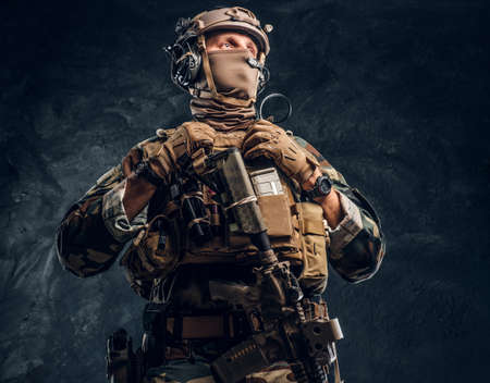 Elite unit, special forces soldier in camouflage uniform. Studio photo against a dark textured wall