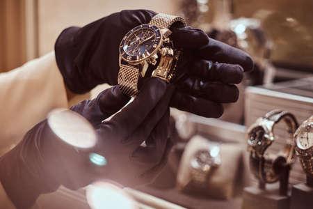 Nahaufnahme der Hände des Verkäufers in Handschuhen zeigt die exklusive Herrenuhr aus der neuen Kollektion im Luxus-Juweliergeschäft