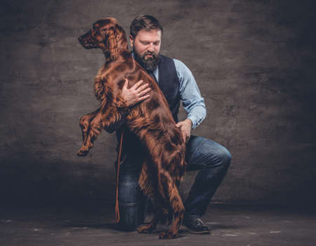 Middle-aged hunter dressed in elegant clothes sits on his knee and holding his purebred brown Setter. Studio photo against a dark textured wall
