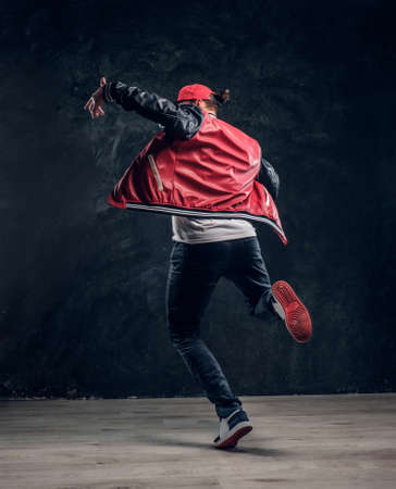 Chico elegante realiza elementos acrobáticos de breakdance. Foto de estudio contra una pared con textura oscura
