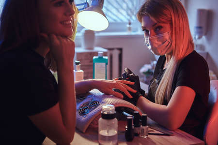 Happy young woman receiving a manicure by a beautician master in the beauty salon. Photo with dim light and red Blue backlight