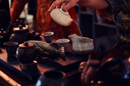 Chinese tea ceremony. Oriental master in kimono pouring a natural tea in the dark room with a wooden interior. Tradition, health, harmony
