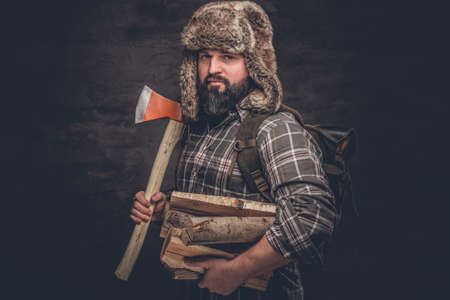Brutal woodcutter with firewood and ax. Studio photo against a dark textured wall Stockfoto