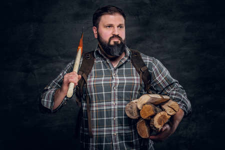 Portrait of a bearded woodcutter with a backpack dressed in a plaid shirt holding firewood and ax. Studio photo against a dark textured wall