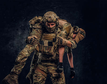 Combat conflict, special mission, retreat. Soldier special forces rescue his wounded teammate carrying him on his shoulders from the battlefield. Studio photo against a dark wall 写真素材 - 119925604