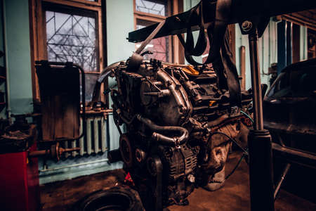 Car engine with hinged equipment suspended on a hydraulic hoist in the workshop 版權商用圖片