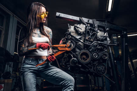 Stylish female model with tattoed body repairs a car engine suspended on a hydraulic hoist in the workshop.