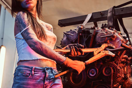 Stylish girl with tattooed body wearing protective goggles working with a car engine suspended on a hydraulic hoist in the workshop. Photo with red light illumination
